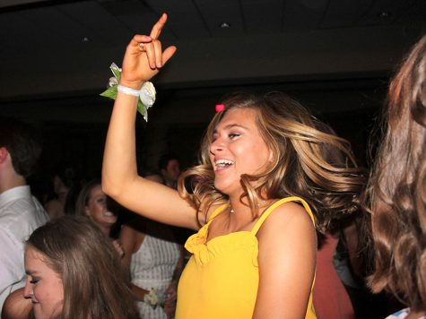 Junior Lily Farkas throws one hand in the air as she dances during the Junior Ring dance at St. Teresa's Academy April 14. The dance was held in the Commons. photo by Meghan Baker