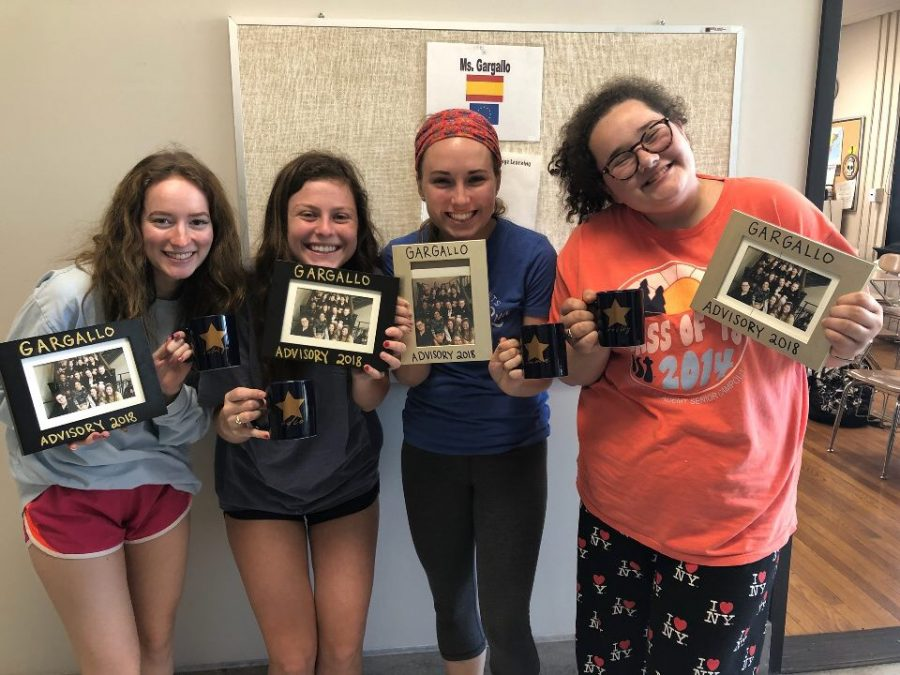 The Gargallo advisory gives their seniors Katelyn Gravely, from left, Edie Livers, Emma Boxx and Reilly Atkins a picture and a mug. Seniors experience their last advisory community day Friday. photo by Kendall Lanier