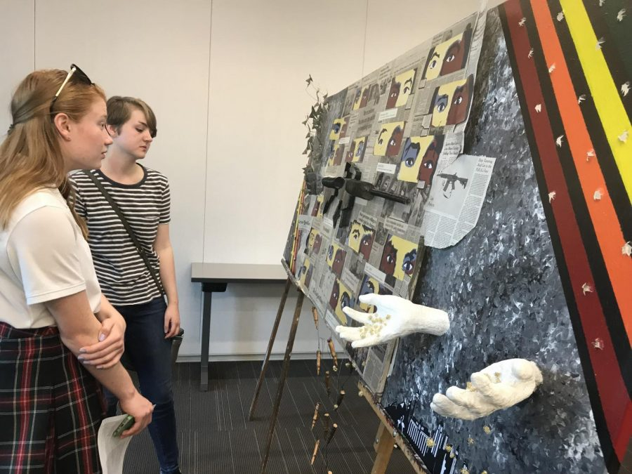 Freshman+Ailis+Reavey+and+senior+Lizzy+Zirkel+observe+Zirkel%27s+and+some+other+students+collaborative+artwork+during+the+Fine+Arts+Showcase+Thursday+in+Windmoor.+The+art+was+a+senior+portfolio.+photo+by+Trang+Nguyen