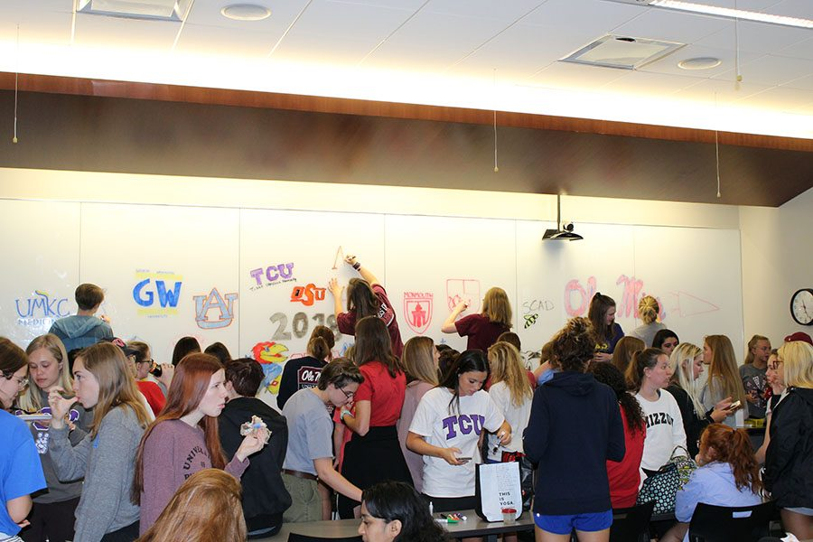 Seniors draw their college logos on the whiteboard during activity May 1. photo courtesy of Megan Schaeffer