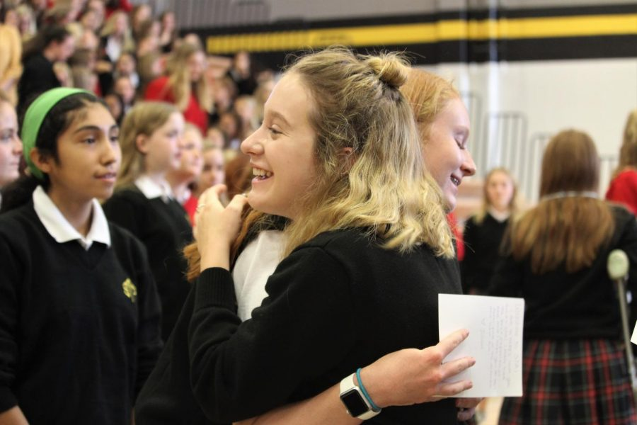 Senior Leah Dorris and freshman Caroline Brincks hug during Passing of the Legacy Aug. 18.  The ceremony is an annual way to begin bonding between upper and underclassmen. photo by Amy Schaffer