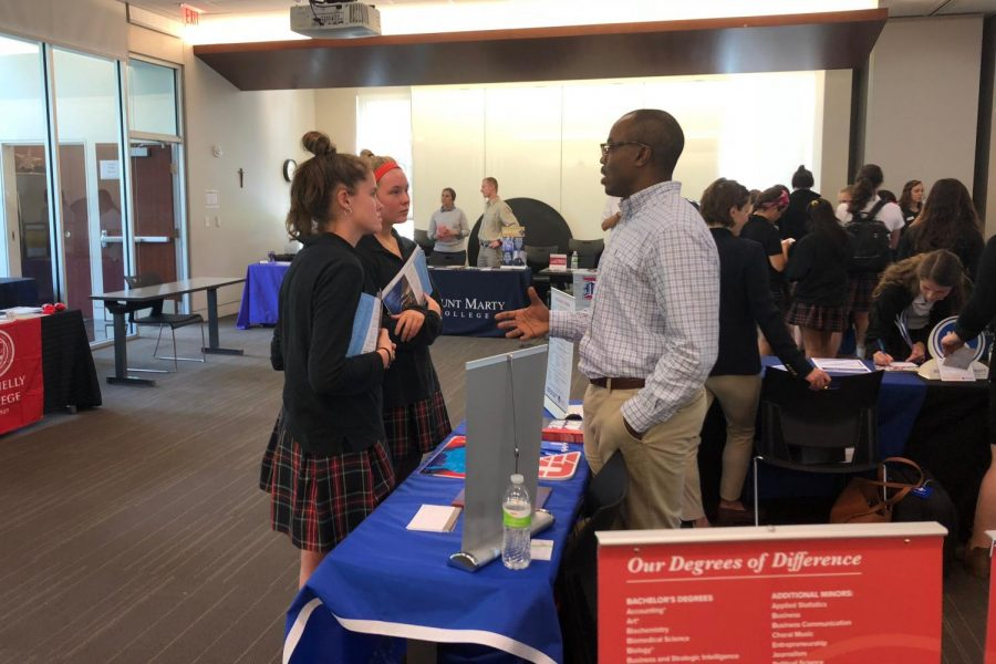 Juniors+Renee+Fortin+and+Lauren+Wittek+speak+with+a+college+representative+Sept.+11.+Over+28+colleges+were+invited+to+attend.+photo+by+Lily+Hart