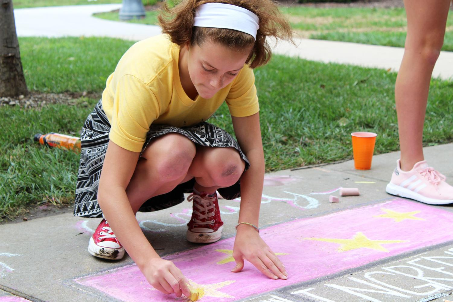 Freshman Ava Kugler draws stars on her advisory's chalk drawing Aug. 29. Freshman wore their STA spirit wear for the first day of Frosh Fest. photo by Rachel Robinson