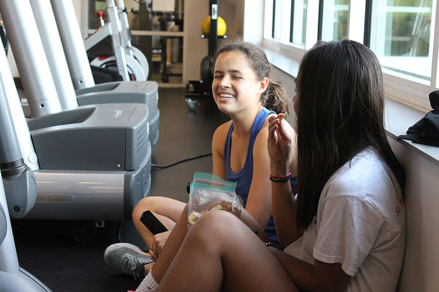 Junior Maura Kugler, left, and Trang Nguyen eat a snack before their cross country practice Aug. 30. The team meets in the weight room for a pre-practice meeting. photo by Maggie Hart