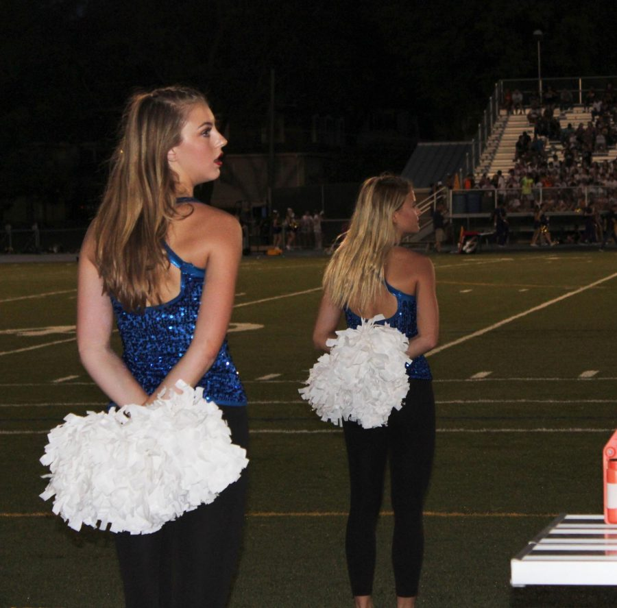 Senior Grace Coleman (left) and sophomore Samantha Amey (right) prepare to take the field Aug. 31. The team danced to a mashup of popular songs. photo by Mckenzie Heffron.