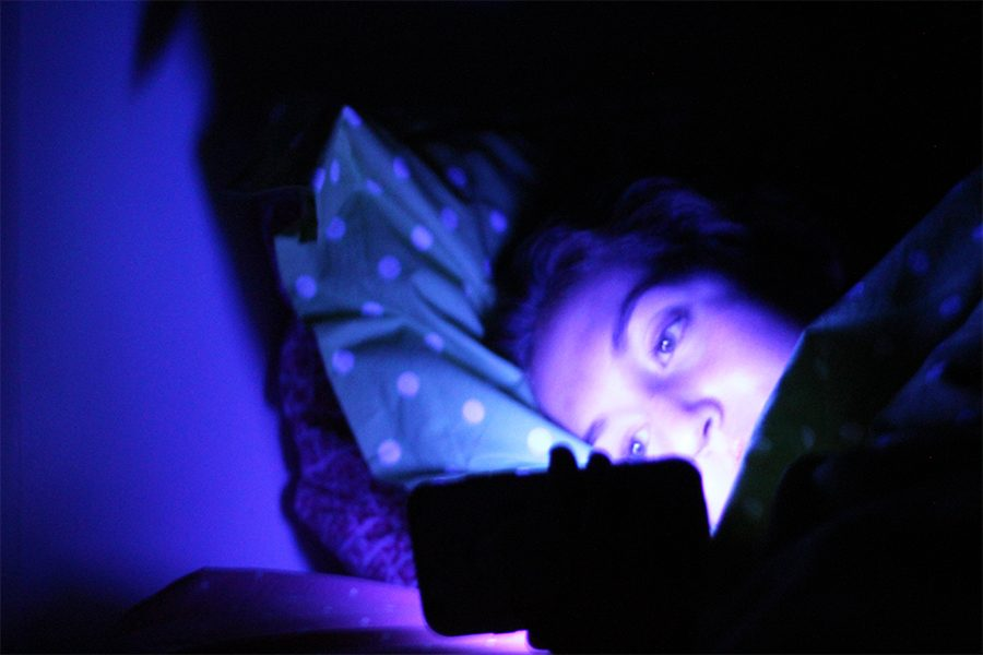 Junior Lauren Fallis lays in bed scrolling through social media at 12 a.m. Aug. 25. Fallis is part of the 70% of high schoolers receiving less than the eight to 10 recommended hours of nightly sleep. photo illustration by Amy Schaffer