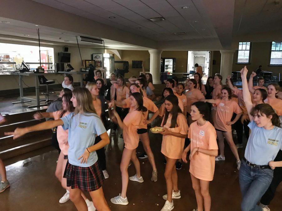 Juniors in blue shirts lead orange-sporting freshmen in
