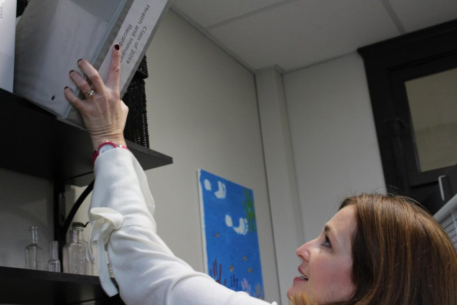Nurse Angela Sweeny pulls down the Class of 2019 Vaccination Records from a shelf in her office Nov. 9. Sweeny often has to access these records to send them to graduated students. photo by Julia Kerrigan