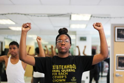 Student Laila Atkins holds up two fists, following her dance instructor's commands Nov. 10. The series of commands walked students through arm, core and leg movements. photo by Amy Schaffer