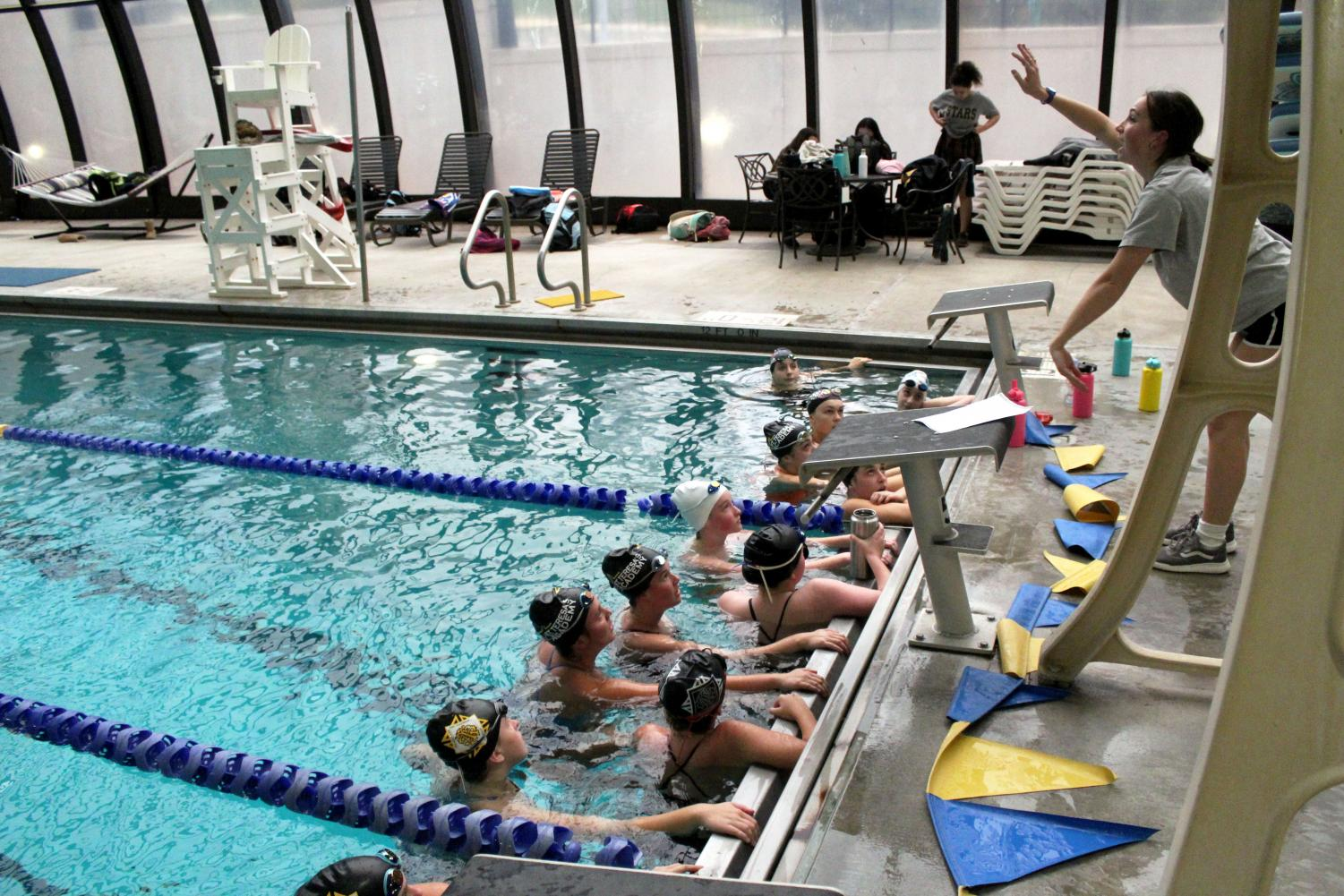 Assistant coach Grace Scovell teaches the swim team a new drill Nov.9. The team had their first practice at University of Missouri-Kansas City. photo by Maggie Hart