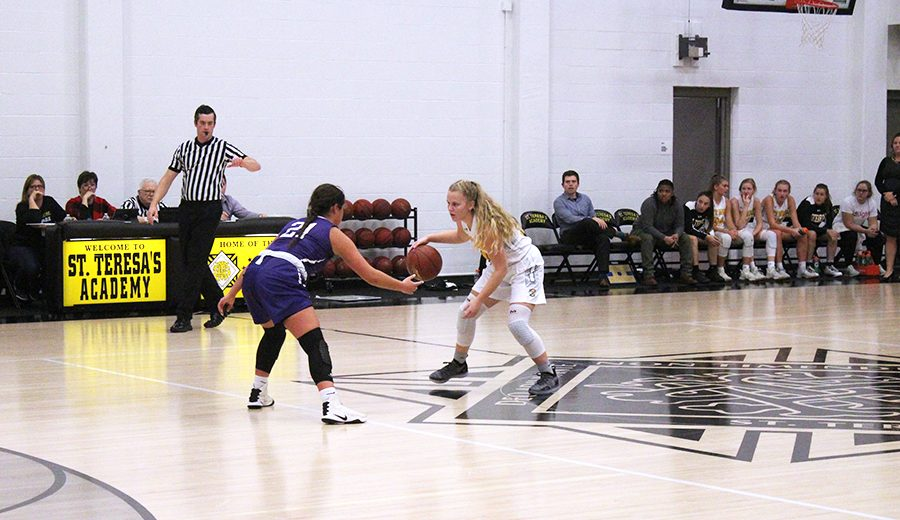 Senior Emily Baldwin dribbles the ball down the court Dec. 4. Baldwin was challenged by a Sion basketball player as she attempted to get the ball to her teammates. photo by Maggie Hart