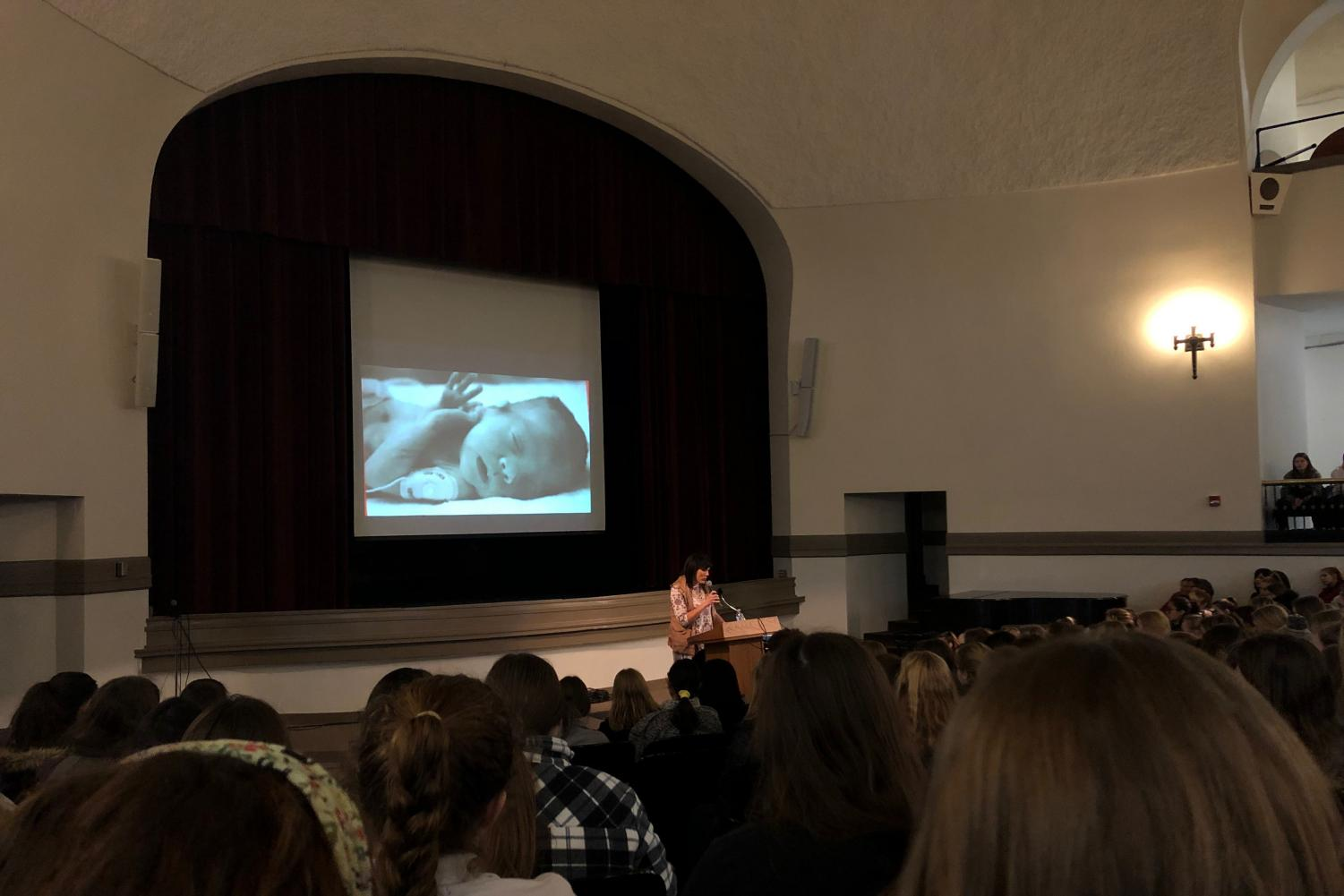 Melissa Ohden speaks to STA students and faculty against a backdrop of her as a baby Jan. 28. Ohden is a Catholic convert and speaks on her life experiences of following God's plan and spreading her message. photo by Lily Hart