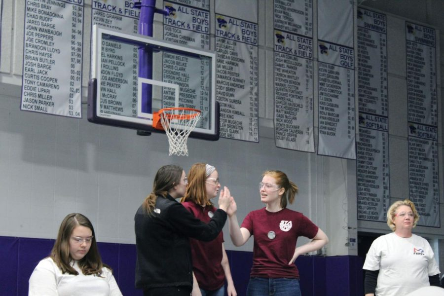Juniors Cecelia Klem, left, and Reagan Penn high-five sophomore Kelsey Raymer during the robotics competition Feb. 9. The robotics competition was held at Blue Springs High School. photo by Olivia Powell