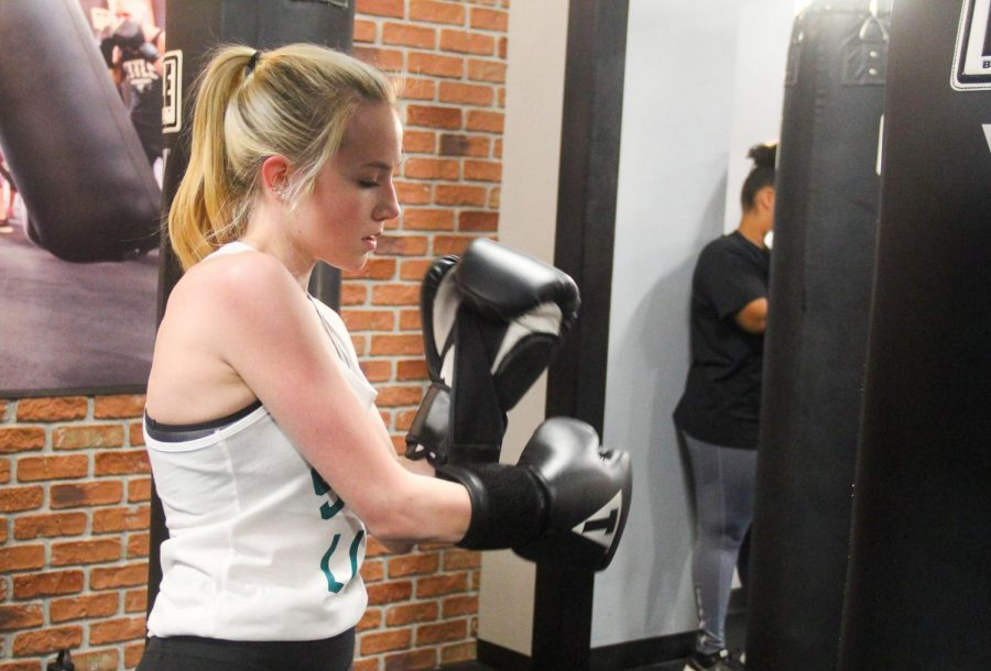Wright+puts+on+her+boxing+gloves.+Classes+at+Title+Boxing+begin+with+7+minutes+of+warm+ups.+photo+by+Rachel+Robinson