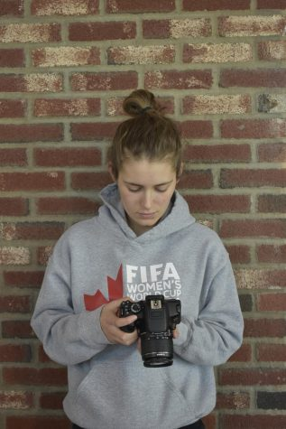 Junior Caroline Scofield, looks at the pictures she has taken on her camera. Scofield takes photos for the Truman social media. photo by Kendall Lanier