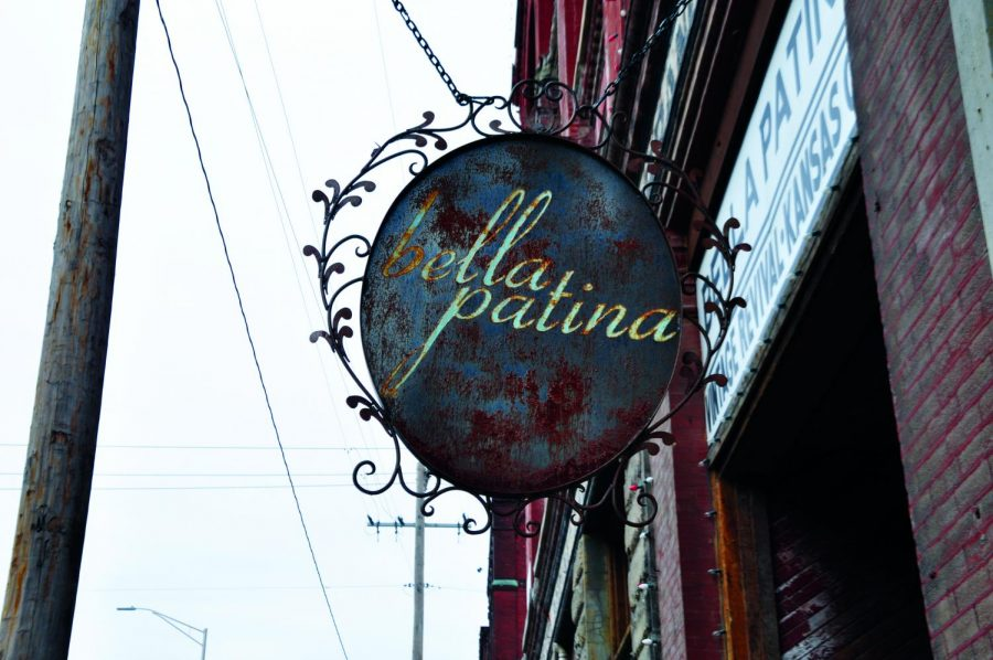 A+weathered+store+sign+hangs+from+the+eaves+of+Bella+Patina+antique+shop+in+the+West+Bottoms+Feb.+28.+photo+by+Gabby+Staker