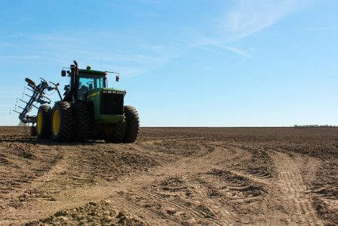 "Richard Budke's tractor sits in a field after the wet winter April 19. The ""terraces"" to drain rainwater and melted snow out of the field were damaged, costing Budke $15,000 to repair."