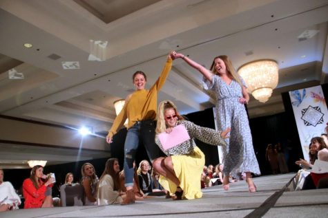 Seniors Reece Knudson, from left, Isabel Shorter and Victoria Parsons walk down the catwalk during the Senior Fashion Show Mar. 31. Shorter dropped to the floor while  Knudson and Parsons raised their hands and walked over her. photo by Tess Jones