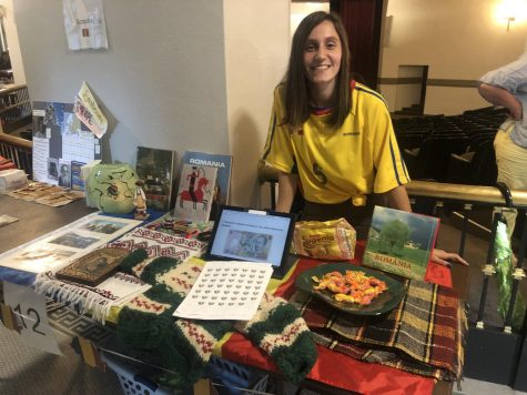 Senior Denisia Pintilie poses with her booth, representing Romania, at International Day Sept. 26. photo by Sophia Durone