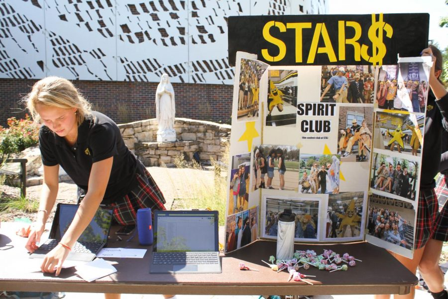 Spirit Club member Elle Schloegel gets her table ready for students to come visit during the club fair Aug. 27. Spirit Club is one of the most popular clubs, so they get many sign-ups each year. photo by Lily Sage