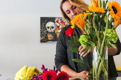 Ad Astra co-owner Sydney Gasper trims the stem off of rose to add to a floral arrangement.