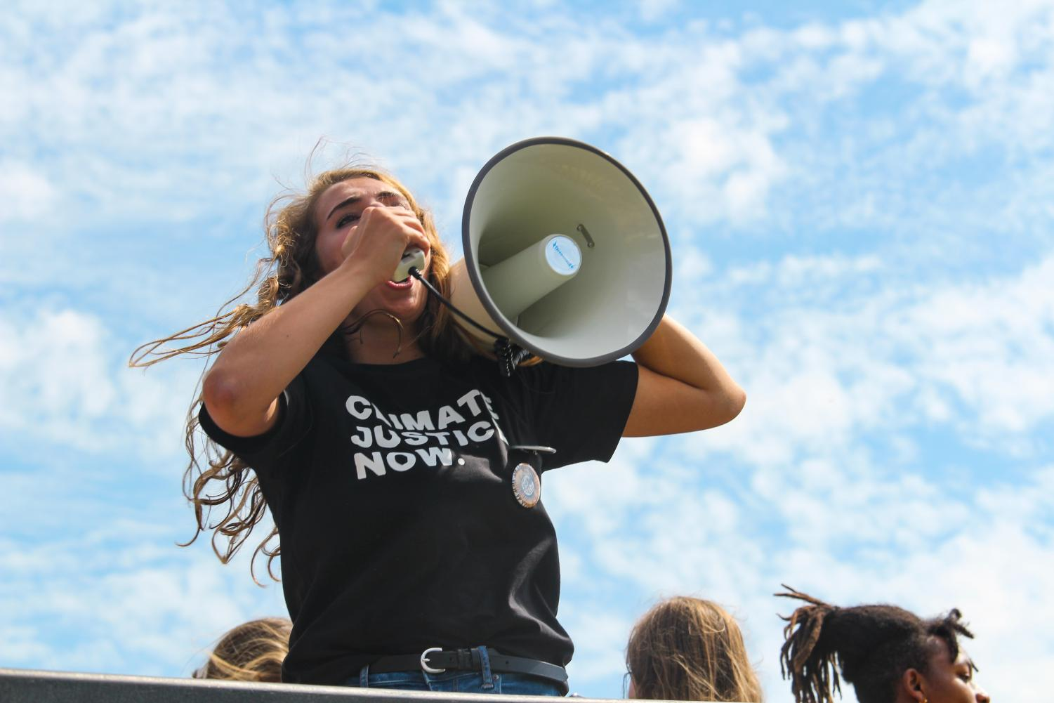 """A Sunrise Movement volunteer leads a """"Green New Deal"""" chant with a megaphone Sept. 20. Protesters chant """"fossil fuels have got to go"""" while marching from James A Theis Park to UMKC. photo by Amy Schaffer"""
