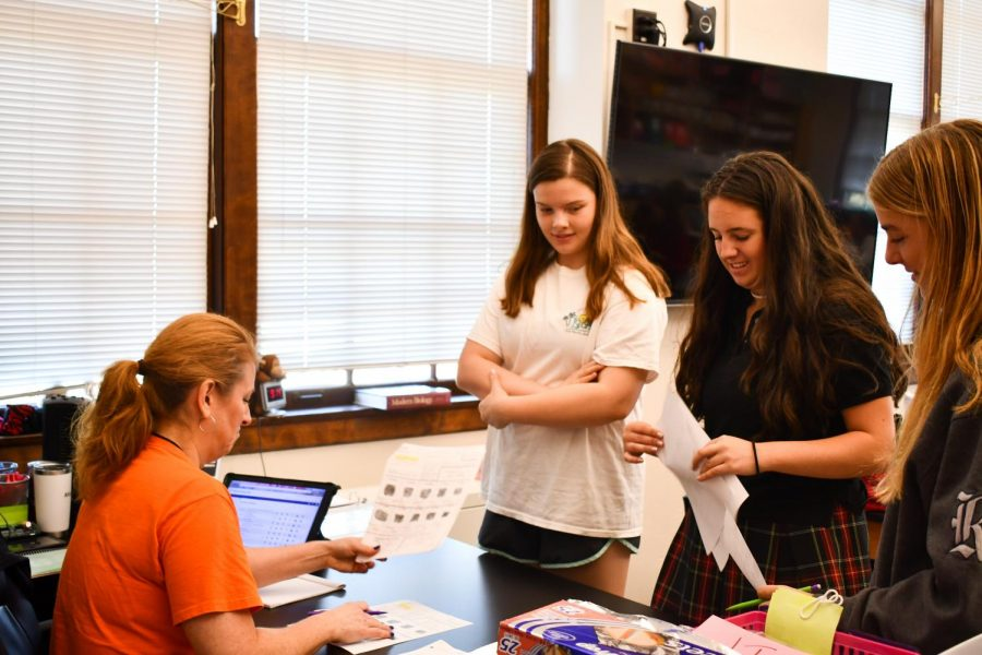 Sophomores Maddison Faul and Kathyrn Hart receive help from Mrs. Blake Sept. 24. In a flipped classroom, students do most of the lecture-based work outside of class and then ask questions during the school day. photo by Lily Sage