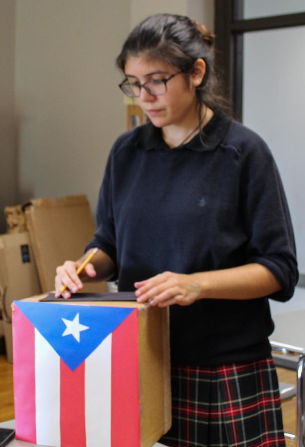 Freshman Isabel Reyes creates a paper window for a Puerto-Rican flag display in the Hispanic Affinity group Sept. 25. Students create a display for Día de los Muertos, Day of the Dead, to be displayed at the Nelson-Atkins Museum of Art. photo by Olivia Powell