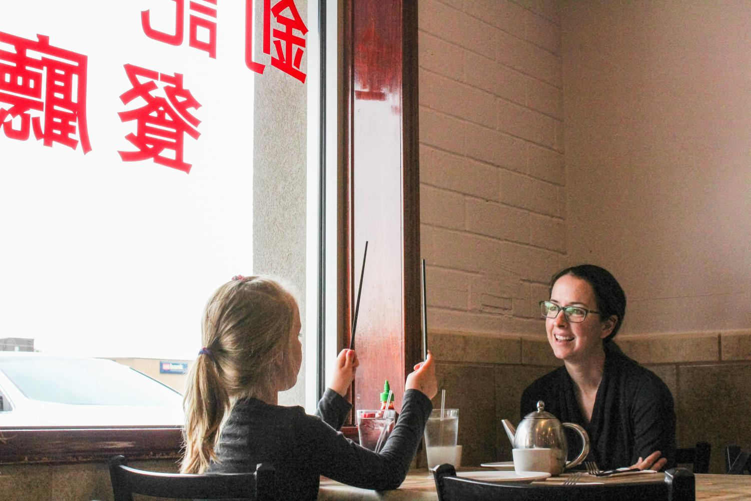 A young girl plays with chopsticks to entertain her mother as they wait for their order.