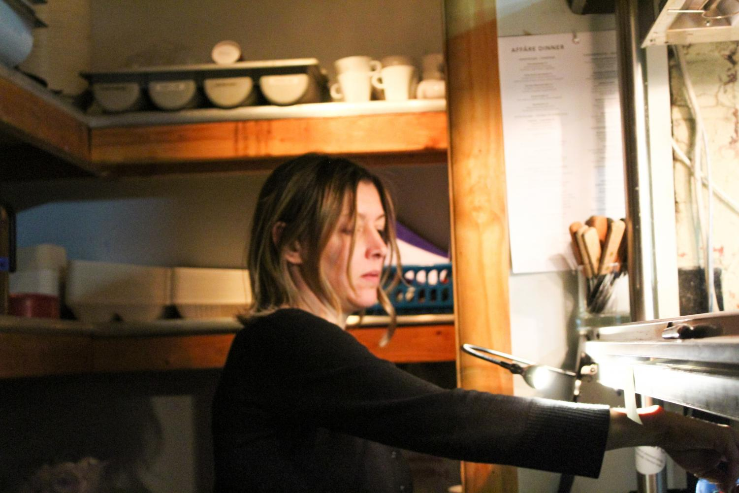 Katrin Hueser, co-owner of German restaurant Affäre, reads order tickets under the window on Nov. 11. Heuser co-owns Affäre with her husband, Martin Heuser. photo by Beatrice Curry