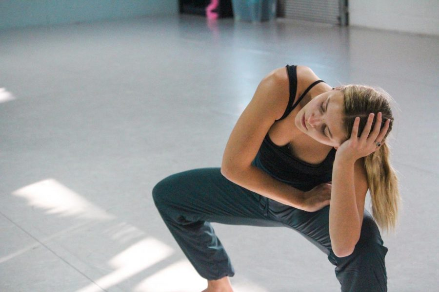Junior Sam Amey hits a resting position Nov. 1. Amey works with her choreographers to experiment with unconventional movement, creating a unique routine. photo by Amy Schaffer