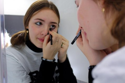 Sophomore Brighid Raymer puts on eyeliner Oct. 31. Her costume was inspired by  e-boy, Rodick Heffely, from the Diary of a Wimpy Kid. photo by Sydney Waldron