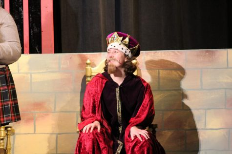 Junior Grace Patenaude smiles during the finale Nov. 5. Patenaude played King Sextimus, a character who did not have lines until the last number. photo by Katie Massman