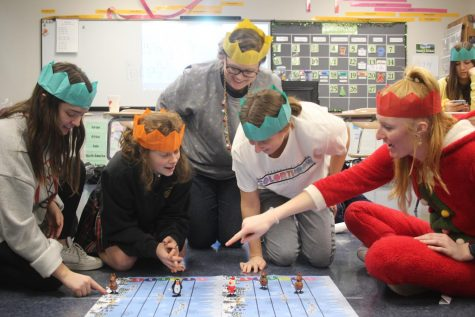 Social studies teacher Alicia Stewart and four of her advisees wear paper crowns while competing in a game Dec. 13. The game and crowns were in their Christmas crackers, a tradition in the Stewart advisory. photo by Katie Massman
