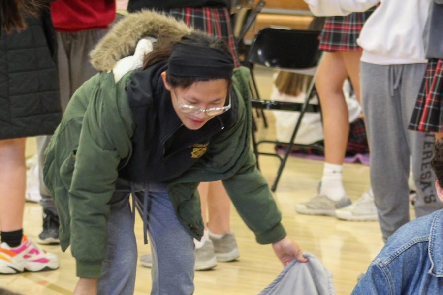 Sophomore+Sing+Piper+spreads+a+blanket+on+the+gym+floor+Nov.+26.+Advisories+brought+blankets+to+the+Thanksgiving+Prayer+Service+and+sat+in+groups+on+the+floor.+photo+by+Iris+Roddy