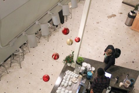 A customer picks up a drink from the coffee bar Dec. 11. This photo was taken from the perspective of the steps to the second floor. photo by Beatrice Curry