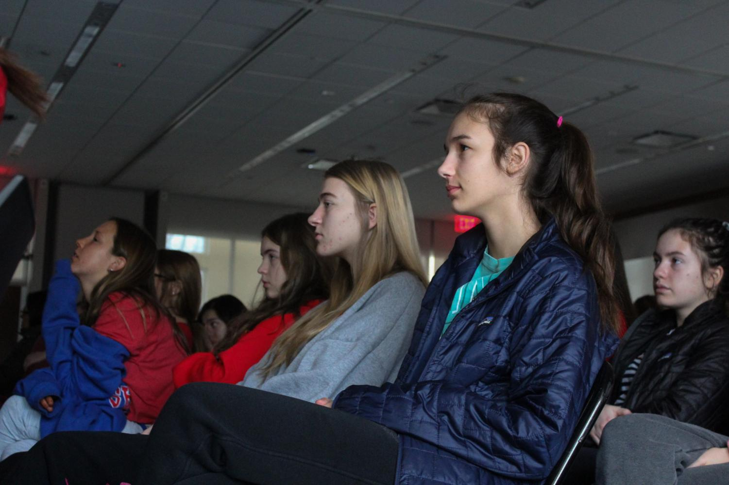 """Sophomores Rachel Pryor, on the left, and Jessie Borchert watch the movie """"True Justice: Bryan Stevenson's Fight for Equality""""  in Windmoor, Jan. 31. This is the fourth year STA has shown a movie to the entire school. photo by Ella Norton"""