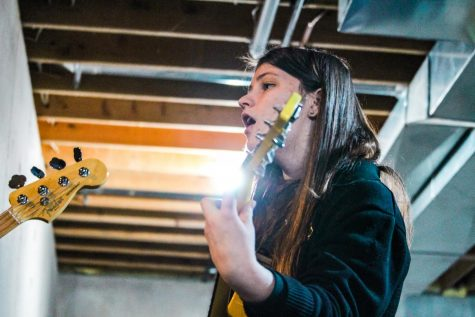 "Senior Kylie Schuster sings and plays guitar while practicing with ""Yellow House"" in her basement Feb. 12. Schuster is the only member of her band to attend STA, so rehearsals are held outside of school. photo by Amy Schaffer"
