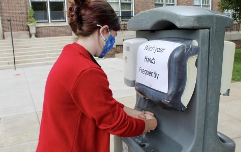 Junior Iris Kline utilizes a hand washing station in the quad Sept. 1. Students are encouraged to frequently sanitize and wash their hands in order to stay as clean as possible. photo by Katie Massman