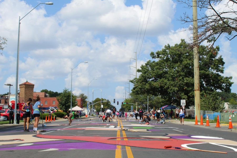 Volunteers continue to work on the street painting at 63rd Street and Troost Sept. 5. Six murals were installed throughout Kansas City over the weekend. photo by Carmon Baker