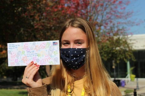 Senior Abby Farmer holds up a decorated envelope containing a letter to prospective voters Oct. 7. Farmer writes letters to important swing states to try and get more people to vote democratic. photo by Katie Massman