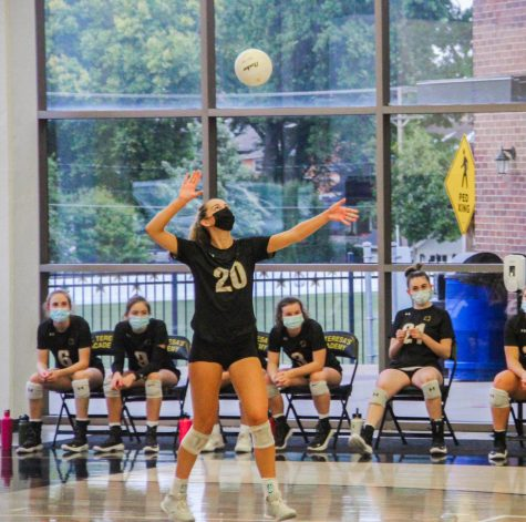 Sophomore Reagan Fox prepares to serve against Bishop Miege High School Sept. 23. Fox has been on varsity since her freshman year, and is an outside hitter. photo by Becca Speier