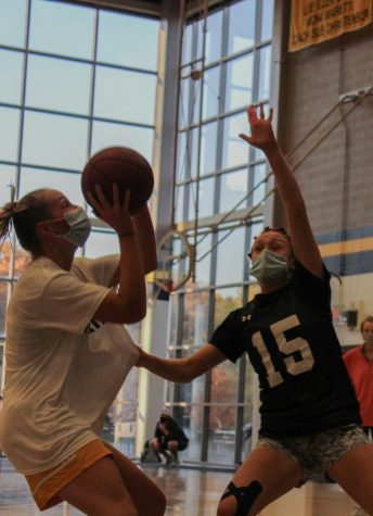 Senior Kate Gibson, left, shooting against junior Grace Quinn at basketball tryouts Oct. 5. Basketball tryouts were held over a five day period of time, and teams were finalized on the fifth day. photo by Sydney Allen