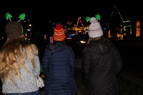 Sophomores, from left, Teresa Elfrink, Stella Hughes and Lucy Doerflinger pause as a car passes in front of a brightly lit house Dec. 13. The street alongside these light displays was packed with cars eager to spend a night of light-watching. photo by Mara Callahan