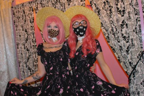 "Two workers at Vetro Vixen, a retro themed store on 39th street, wear pink wigs and dresses in preparation for the holiday Jan. 28. Pink is thought to have a calming effect, and one shade known as ""drunk-tank pink"" is sometimes used in prisons to calm inmates. photo by Sydney Waldron"