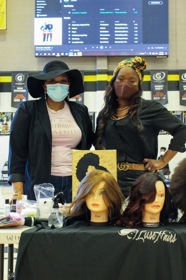 Lusette Walker, right, stands with her partner in front of their demonstration table Feb. 23. Walker has owned Luse Hair Salon for 12 years and it is located on the corner of Grand Blvd. and 20th St. photo by Sydney Allen