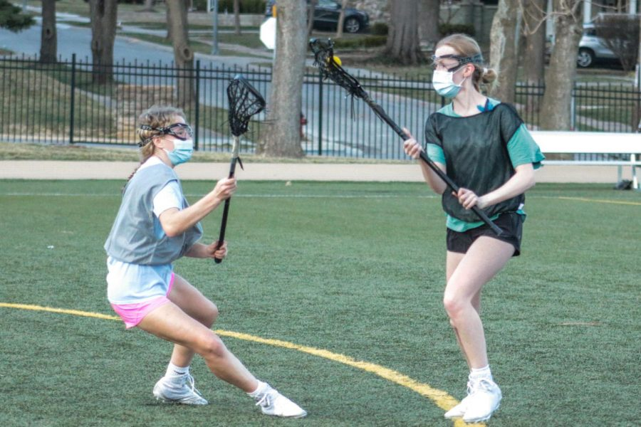 Sophomore Maggie Reintjes guards junior Grace Uecker during a varsity lacrosse practice drill March 10. A command was yelled by one of the coaches giving the players instructions as the offensive players tried to move towards the lacrosse goal.