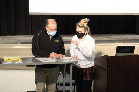 Senior Liv Collet and music teacher Steve Perry go over the sheet music at the front of the auditorium in the Music and Arts building Feb. 24. Together, they had worked on the parts of the song that Collet had questions on. photo by Ali Madden