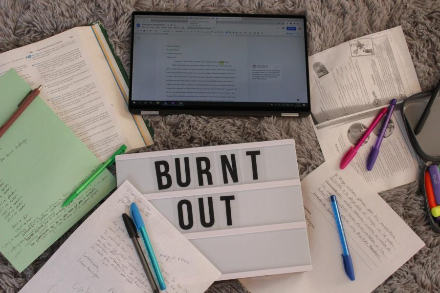"""A pile of homework materials sit around the words """"burnt out"""" April 1. Student burnout is becoming a trend on social media platforms such as TikTok and Instagram. photo illustration by Sydney Allen"""