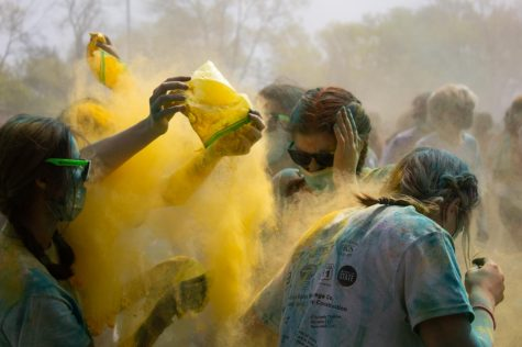 Yellow powder is thrown onto an unsuspecting group of friends April 26. The Color Throw is an annual tradition that happens near the end of the school year.